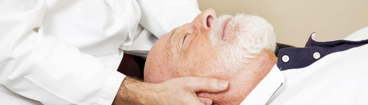 Closeup of a chiropractor adjusting a senior patient's cervical spine (neck).